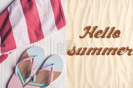 Flip flops and towel on sandy beach with hello summer inscription