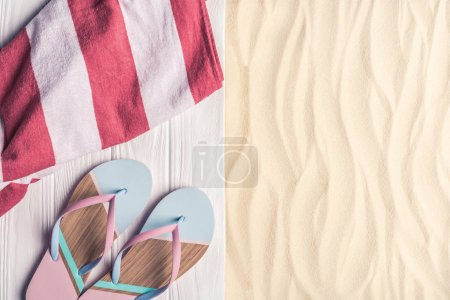 Photo for Flip flops and towel on light sand - Royalty Free Image