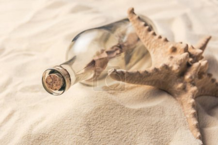 Bottle with letter and starfish on sandy beach