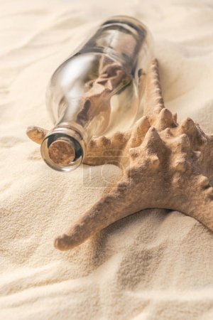 Corked bottle with message and starfish on light sand