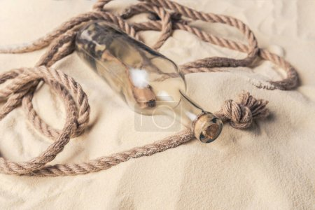 Corked bottle with message and rope on sandy beach