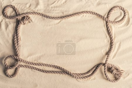 Frame of ship rope on sandy beach