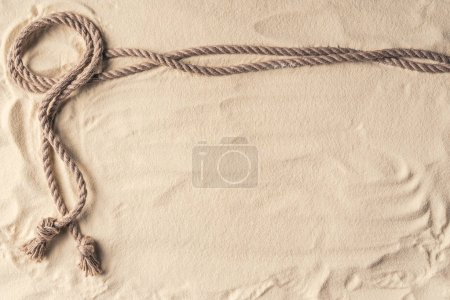 Photo for Knotted rope frame on light sand - Royalty Free Image