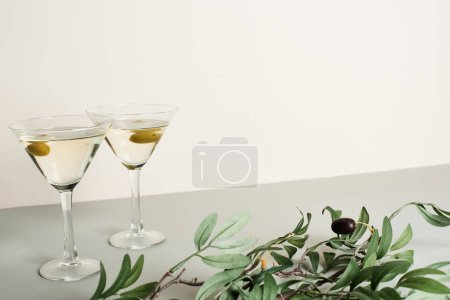 Photo for Two glasses with cocktails and olive branch on grey surface isolated on white - Royalty Free Image