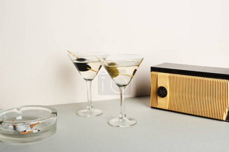Photo for Martini cocktails with ashtray and cigarette butts and vintage radio on white background - Royalty Free Image