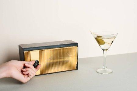 Photo pour Vue recadrée de la femme ajustant le volume de la radio rétro avec cocktail martini à côté - image libre de droit