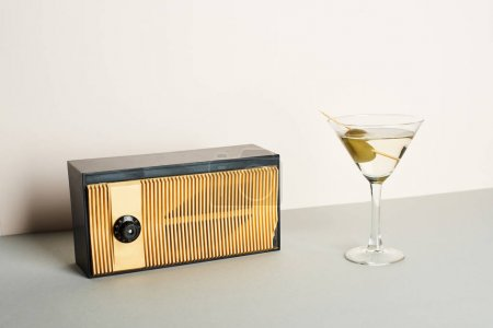 Photo for Vintage radio with glass of martini cocktail on grey surface - Royalty Free Image