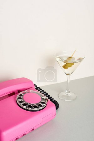 Photo for Vintage pink telephone with glass of cocktail on white background - Royalty Free Image