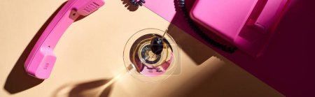 Top view of martini in glass with pink telephone on colorful background, panoramic shot
