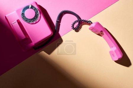 Photo pour Vue du dessus du téléphone rose avec ombre sur une surface colorée - image libre de droit