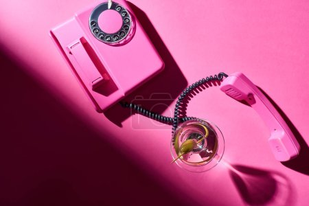 Photo for Top view of martini in glass with retro telephone on pink background - Royalty Free Image