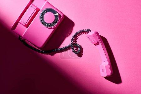 Photo pour Vue du dessus du téléphone rose vintage avec ombre sur une surface lumineuse - image libre de droit