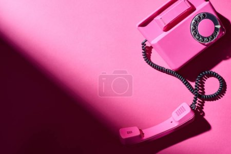 Photo for Top view of pink telephone with shadow on bright surface - Royalty Free Image
