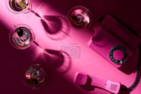 Photo pour Vue en haut des cocktails de martini et du téléphone rétro sur fond rose - image libre de droit