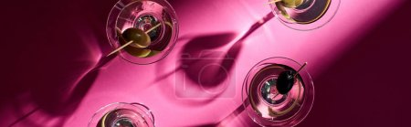 Top view of martini with olives on bright pink background, panoramic shot