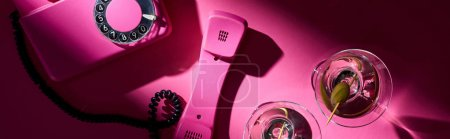 Photo for Top view of vintage telephone and two martini cocktails on pink background, panoramic shot - Royalty Free Image