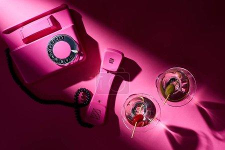 Foto de Vista superior del teléfono de época y cócteles con sombras en el fondo rosa. - Imagen libre de derechos