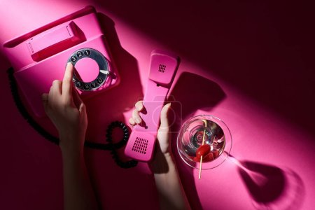 Photo for Cropped view of woman using vintage telephone beside cocktail on pink background - Royalty Free Image