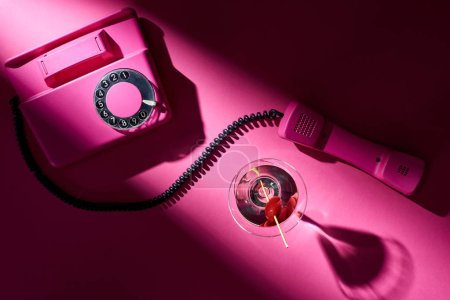 Photo for Top view of vintage telephone and cocktail with shadow on pink background - Royalty Free Image