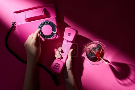 Photo for Cropped view of woman using retro telephone with martini beside on pink background - Royalty Free Image
