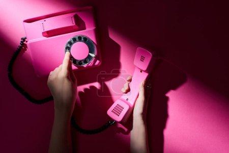 Photo pour Vue agrandie d'une femme utilisant un téléphone rétro sur fond rose - image libre de droit