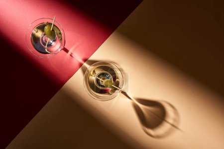 Top view of martini with olives on red and beige background