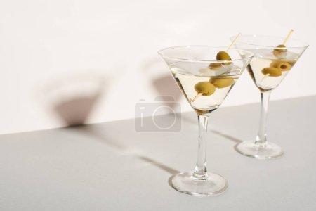 Photo pour Cocktails Martini aux olives sur fond blanc - image libre de droit