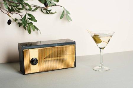 Photo pour Radio vintage avec martini et branche d'olivier sur fond blanc - image libre de droit