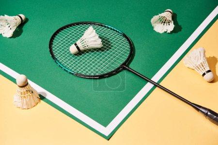 Photo pour Vue grand angle de la raquette de badminton et des navettes sur fond vert et jaune - image libre de droit