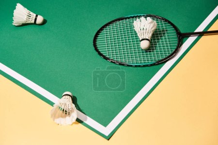 Photo pour Vue à grand angle de raquettes et de navettes de badminton sur la cour verte à la surface jaune - image libre de droit