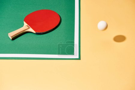 Photo for High angle view of tennis racket on table and ball on yellow surface - Royalty Free Image