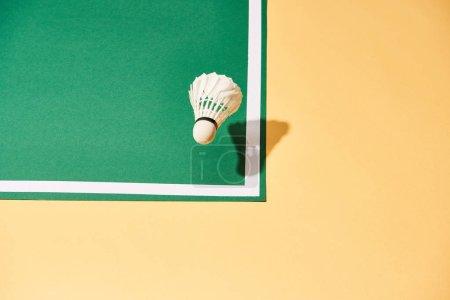 Photo pour Vue à grand angle de la navette de badminton sur la cour verte et la surface jaune - image libre de droit