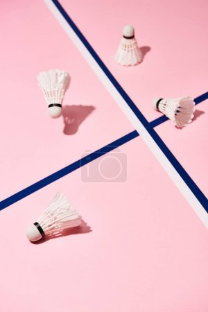 Photo pour Navettes de badminton avec ombre sur surface rose avec lignes bleues - image libre de droit