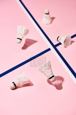 Photo for Badminton shuttlecocks on pink surface with blue lines - Royalty Free Image