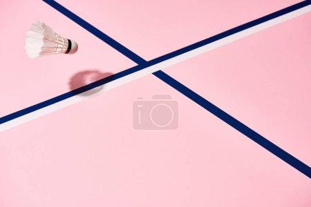 Photo pour Navette de badminton sur surface rose avec lignes bleues - image libre de droit