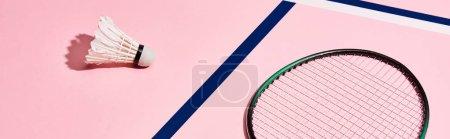 Photo pour Raquette de badminton et volant sur fond rose avec lignes bleues, prise de vue panoramique - image libre de droit