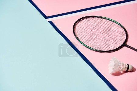 Photo pour Raquette de badminton et volant sur une surface colorée aux lignes bleues - image libre de droit