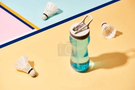 Photo pour Bouteille d'eau et navettes de badminton à la surface avec des lignes colorées - image libre de droit