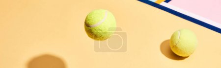 Two tennis balls with shadow on colorful background with blue lines, panoramic shot