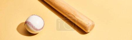 Photo pour Batte de baseball et balle sur fond jaune, tir panoramique - image libre de droit