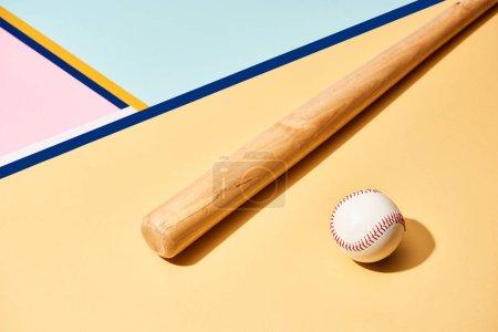 Photo pour Bâton et balle de baseball en bois sur fond coloré avec des lignes - image libre de droit
