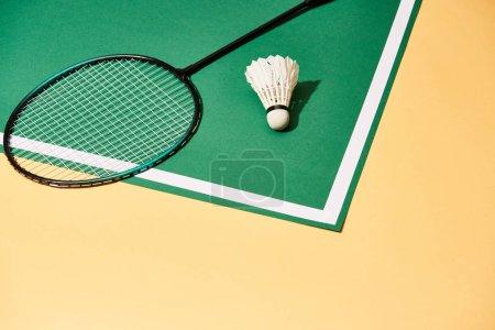 Photo pour Raquette de badminton en métal et volant sur aire de jeux avec ligne et surface jaune - image libre de droit
