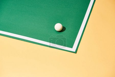 Photo for Table tennis ball with shadow on green and yellow background - Royalty Free Image