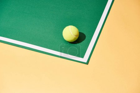 Tennis ball with shadow on green and yellow surface with white line