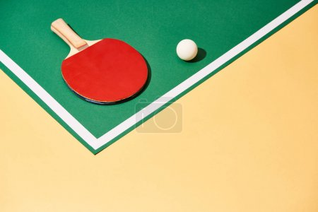 Photo for Table tennis racket and ball on green and yellow surface with white line - Royalty Free Image