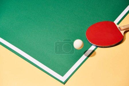 Photo pour Raquette de balle et de ping-pong sur surface jaune et verte - image libre de droit