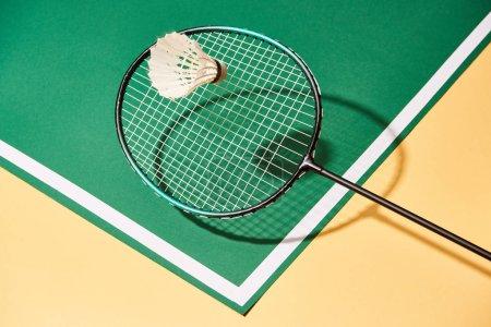 Photo pour Raquette de badminton et volant sur surface verte et jaune avec ligne - image libre de droit
