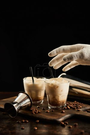 Foto de Decorative hand above white russian cocktail in glasses with straws on wooden board with coffee grains isolated on black - Imagen libre de derechos