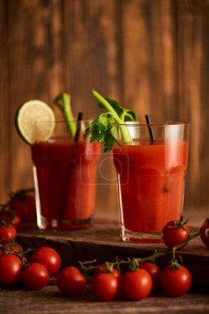 Photo pour Foyer sélectif de cocktail Mary sanglant dans des verres à la chaux et au céleri sur fond de bois avec des tomates - image libre de droit