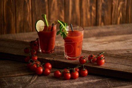 Photo pour Cocktail Mary sanglant dans des verres à la chaux et au céleri sur fond de bois avec tomates - image libre de droit
